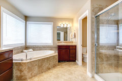 Modern bathroom with round tub and shower. Beige bathroom with windows, cherry wooden cabinets, glass door shower and toilet. View of round white bath tub royalty free stock photos