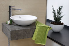 Modern bathroom sink. Interior of a modern hotel bathroom representing a sink with a towel and a plant in background stock photo
