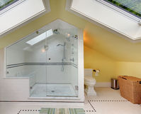 Modern bathroom upstairs with large shower and vaulted ceiling. royalty free stock image