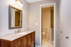 Modern bathroom with vanity cabinet, granite counter top and mirror. Stock Photography
