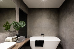 Modern bathroom wall made in dark color tiles Stock Photos