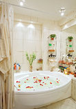 Modern bathroom in warm tones with jacuzzi. And rose petals wide angle view Royalty Free Stock Photo