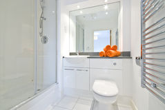 Modern bathroom in white large shower room. Contemporary en-suite bathroom shower room with ceramic hand wash basin, toilet and orange towels in white Stock Images