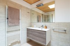 Modern bathroom with wood and marble finishes royalty free stock image