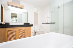 Modern bathroom with wooden cabinetry Stock Images