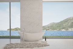 Modern bathtub against large window with seascape view Royalty Free Stock Images