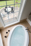 Modern bathtub overlooking a brick patio Royalty Free Stock Photos