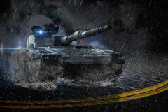 Modern battle tank moving at night in the rain Royalty Free Stock Photo