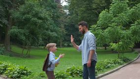 Modern beard father giving a hi-five his little son in the park. Dad meets his son from elementary school. the end of. The school day concept stock footage