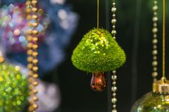 Modern beautiful Christmas tree toy in the form of a mushroom. Selective focus green background. Modern beautiful Christmas tree toy in the form of a mushroom Royalty Free Stock Image