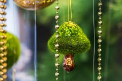 Modern beautiful Christmas tree toy in the form of a mushroom. Selective focus green background. Modern beautiful Christmas tree toy in the form of a mushroom Royalty Free Stock Images