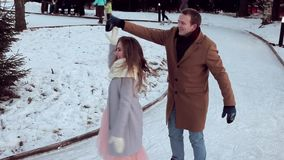 Modern beautiful couple having fun skating on the outdoor rink in winter. Winter couple smiling happy in Valentine`s day. Beautiful young couple skate on outdoor stock footage