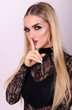 Modern and beautiful girl close-up puts finger to his lips Stock Photo