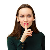 Modern and beautiful girl close-up puts one finger to his lips in sign of silence stock photos