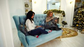 Modern beautiful girl sisters for gadgets do their own business, sitting on couch in bright living room with festive stock video