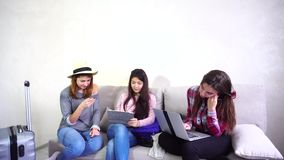 Three young women sisters use gadgets and communicate with each other, sitting on sofa in room during day. Modern and beautiful girls hold hands in their hands stock video