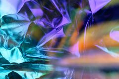 Modern beautiful holographic background of crumpled foil. Trendy 80`s style. Modern beautiful holographic background of blurred crumpled foil. Trendy 80`s style royalty free stock photo