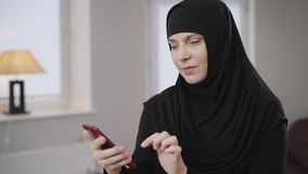 Modern beautiful muslim woman in traditional hijab looking at smartphone screen and smiling. Positive lady using social