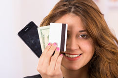 Modern beautiful young woman holding cell phone. Closeup portrait ofmodern beautiful young smiling woman holding cell phone, money and credit card in front of Stock Images