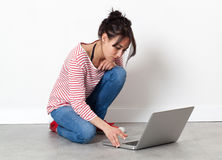 Modern beautiful young woman sitting on the floor, working Royalty Free Stock Photo