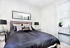 Modern bed close up with black mattress beside the bathroom Royalty Free Stock Photos