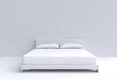Modern bed with two pillows against the wall of the room. Royalty Free Stock Photography