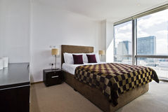 Modern bedroom. Contemporary double bedroom with floor to ceiling windows and city views Stock Image