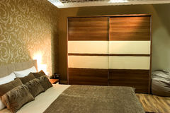 Modern bedroom. With brown wardrobe and bed with two pillows stock photo