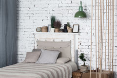 Modern bedroom with big grey bed in middle royalty free stock photography