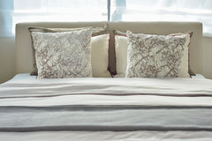 Modern bedroom brown pattern pillows on bed Stock Photography