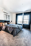 Modern bedroom with a carpet floor space illuminated using sunli Stock Photography