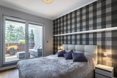 Modern bedroom with checker pattern. On the wall and big window royalty free stock photos