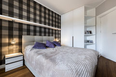 Modern bedroom with checker pattern. On the wall and wardrobe royalty free stock image