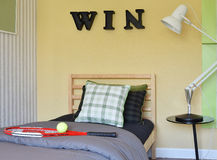 Modern bedroom decorative with racquet and tennis ball. Modern bedroom interior decorative with racquet and tennis ball on wooden bed Royalty Free Stock Photos