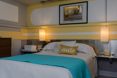 Modern Bedroom. A dimly lit contemporary bedroom in yellow and turquoise with designer shapes painted on the walls Royalty Free Stock Image