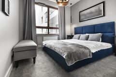Modern bedroom with blue bed royalty free stock image