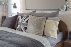 Modern bedroom with gray pillow and lamp on wooden bedside table Royalty Free Stock Image