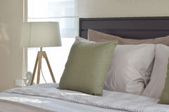 Modern bedroom with green pillow and decorative wooden lamp Stock Photography