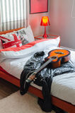 Modern bedroom with guitar and jacket on white bed Stock Photography