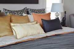 Modern bedroom interior with orange and gold pillows on bed Royalty Free Stock Photo