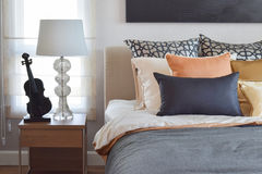Modern bedroom interior with orange and gold pillows on bed and  table lamp. Modern bedroom interior with orange and gold pillows on bed and bedside table lamp Royalty Free Stock Photo