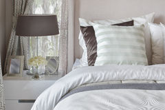 Modern bedroom interior with striped pillow on bed and bedside table lamp Stock Images