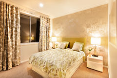Modern bedroom with king size bed illuminated by table lamps Stock Images