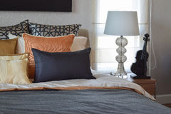 Modern bedroom with orange and gold pillows on bed. Modern bedroom interior with orange and gold pillows on bed and bedside table lamp Stock Images