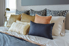 Modern bedroom with orange and gold pillows on bed and. Modern bedroom interior with orange and gold pillows on bed and bedside table lamp Stock Photos