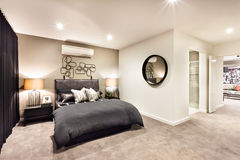 Modern bedroom with a round mirror and hallway Stock Photography