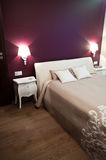 Bedroom. A modern bedroom with violet walls Royalty Free Stock Photography