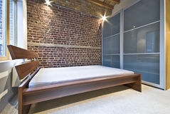Modern bedroom in warehouse conversion. With exposed brick wall, large modern wardrobe and king size wooden bed stock image