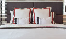 Modern bedroom with white and striped pillows on bed Royalty Free Stock Photography