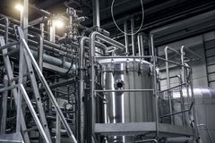 Modern beer factory, brewery. Steel tanks and pipes for beer production. Industrial background. Modern beer factory, brewery concept. Steel tanks and pipes for Stock Photo